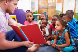 A child care assistant and children in a class section