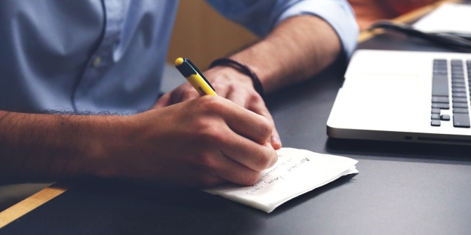 A man taking notes on a piece of paper