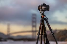 Camera on a tripod with a blurred bridge on the background