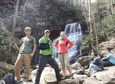 group picture of three people standing in front of waterfall