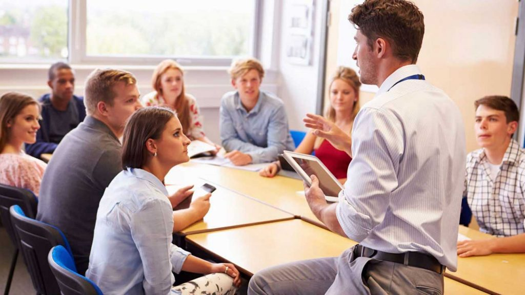 A young man with white shirt and an ipad un hands explaining something to a group of students surrounding a table