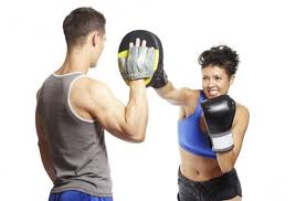 A young man and a young woman in sports clothes practicing boxing with black gloves