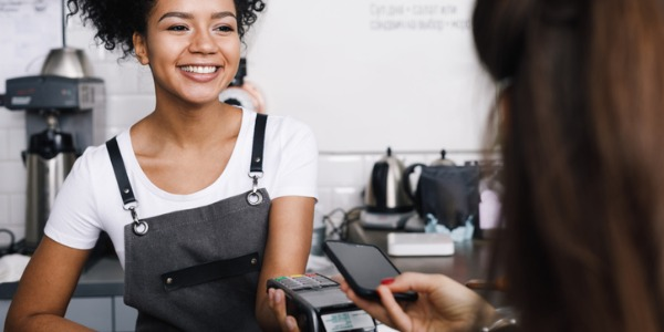 a young woman with black hair and an apron processing a payment from a woman paying with her smartphone