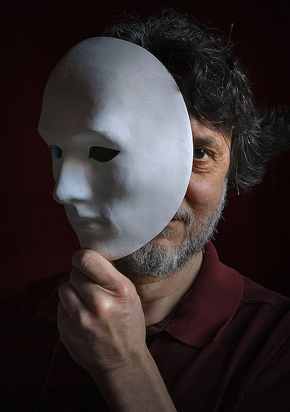 Man holding a mask over his face