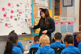 This image portrays a student worker in an early childhood classroom.