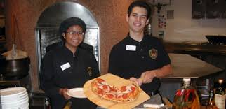 Here, a student worker has completed baking a pizza.