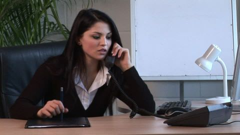 A young woman with black hair and black suit speaking on the phone on a front desk