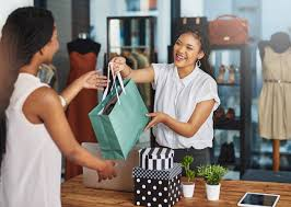 Retail worker completing a sales transaction by handing a shopping bag to the customer