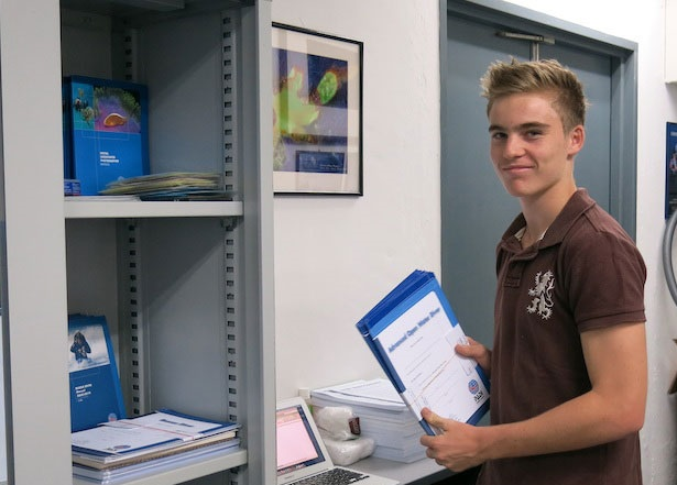 a young blonde man with brown shirt holding a blue tablet with white paper in an office with a shelve full of papers and a photocopy
