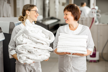 A young woman with glasses and white uniform holding a pile of white sheets speaking with a fellow worker with white uniform holding white towels