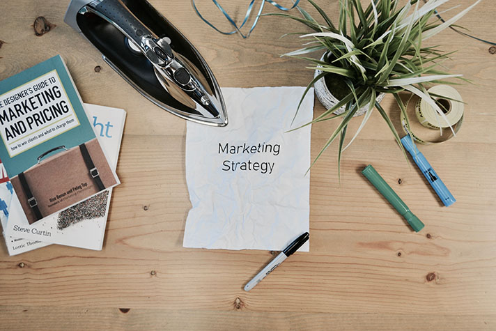 Photo of a desk with various desk ornaments and a sheet of paper with the writing marketing strategy in the center