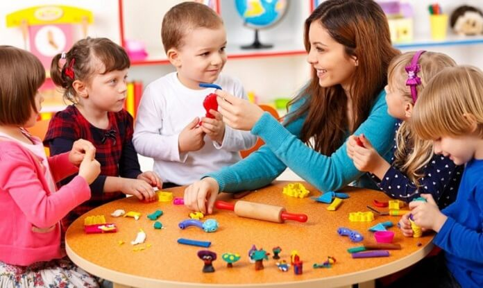 a young woman with brown hair and a blue shirt taking care of children playing with LEGOS in an orange table