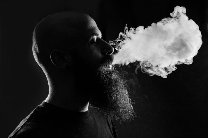 black and white image of a bearded man exhaling smoke