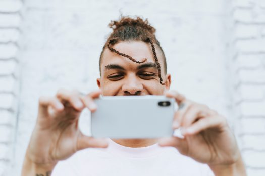 young man using phone to watch videos