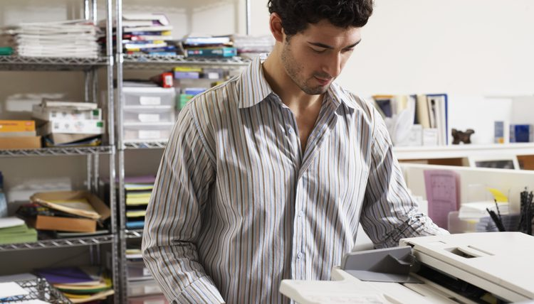 A young man with black hair and a shirt working with the photocopier in an office full of office materials