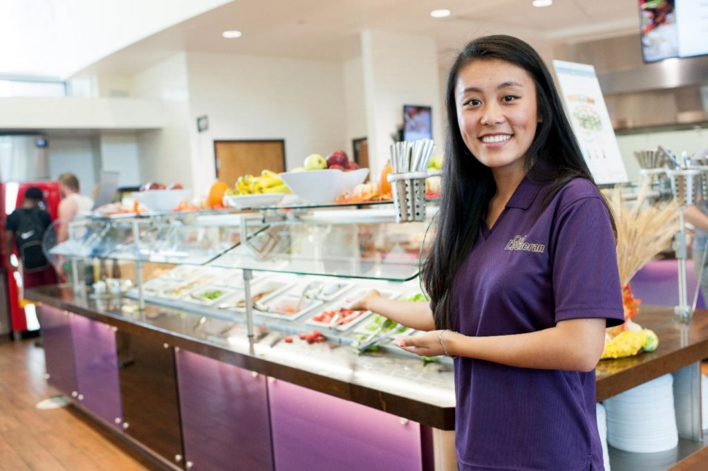 A girl standing at fresh salad bar
