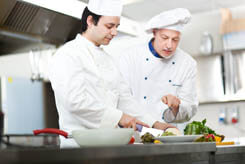 A young and an old chef working together making a plate of food
