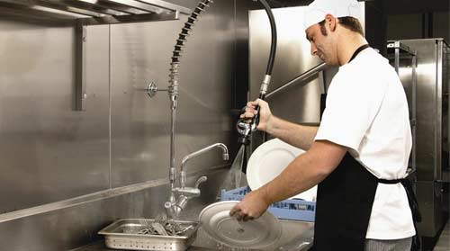 A young man with black hair, a white uniform with white cap and a black apron washing dishes in a kitchen