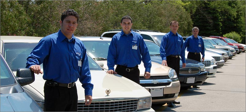 Four men in blue shirts uniforms in a parking lot taking care of the vehicles