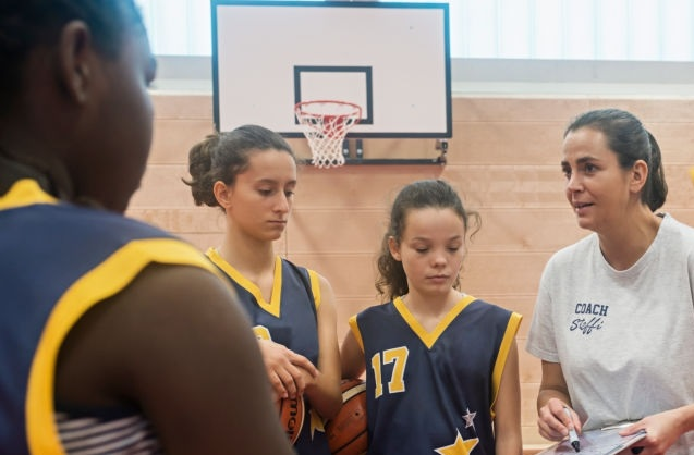 A young woman with black hair and grey shirt coaching a girls basketball team