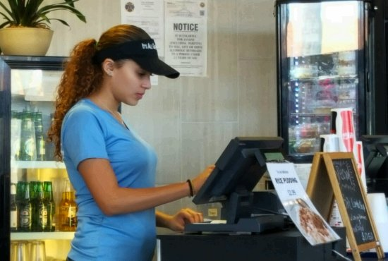 A young girl with brown hair, blue shirt and black cap working with a cashier with a beverage fridge behind