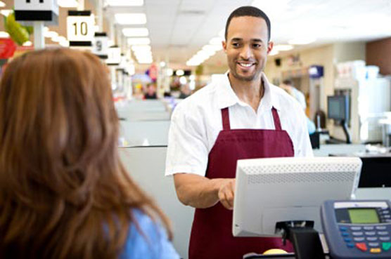 A young man with black hair, a white shirt and a wine apron working with the cashier and helping a woman of brown hair and blue shirt