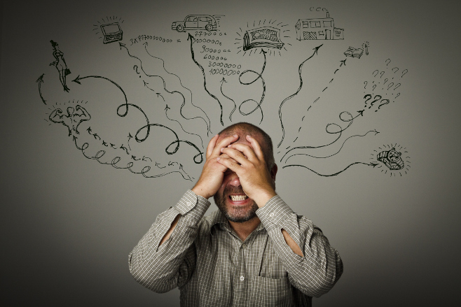 image of man holding his head in stress
