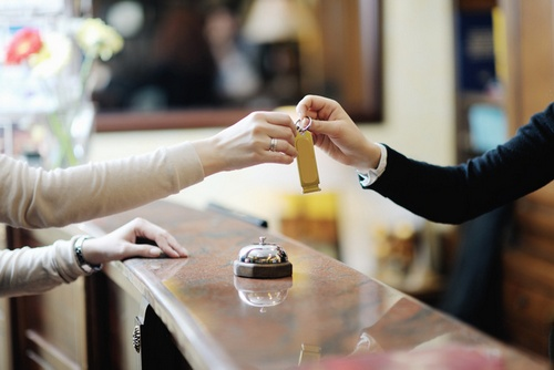 A hand of a front desk worker with black sleeve giving a key to the hand of a customer in a front desk