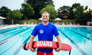 A young man with blonde hair, a blue shirt and red shorts holding a guard red float in front of a pool
