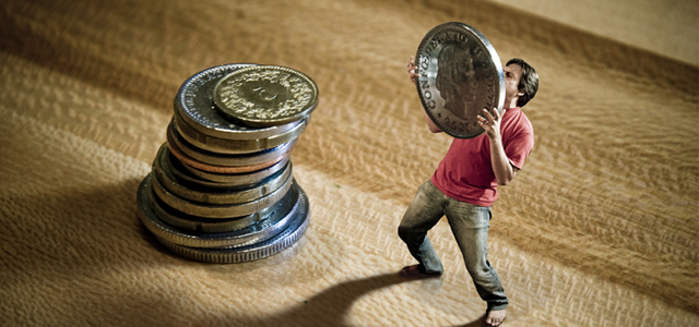 miniature man piling up coins to manage his finances