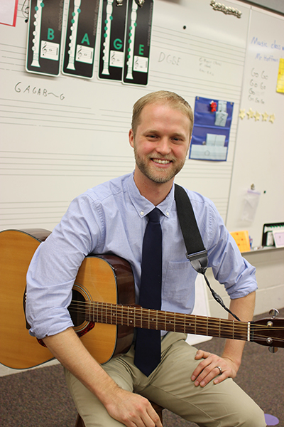 A young man with blonde hair, blue shirt and khaki pants holding a guitar in a music classroom