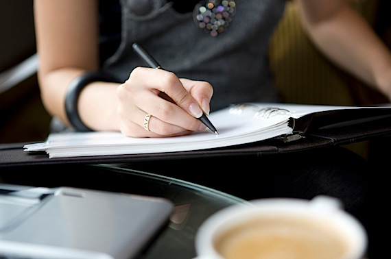 A Young Woman With black shirt and a pen in her hand writing in a notebook on a table with a coffee
