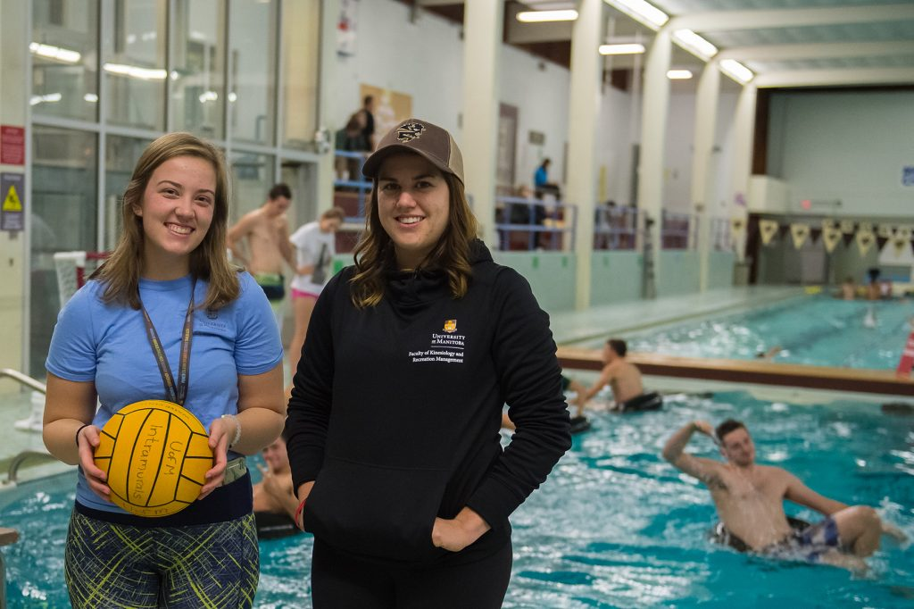 A young girl with brown hair and blue shirt holding a yellow volleyball ball with another girl of brown hair, black cap and black sweater whit swimming pool behind