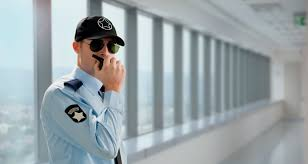 A young security officer with blue shirt uniform, black cap and black sunglasses speaking with a walkie-talkie