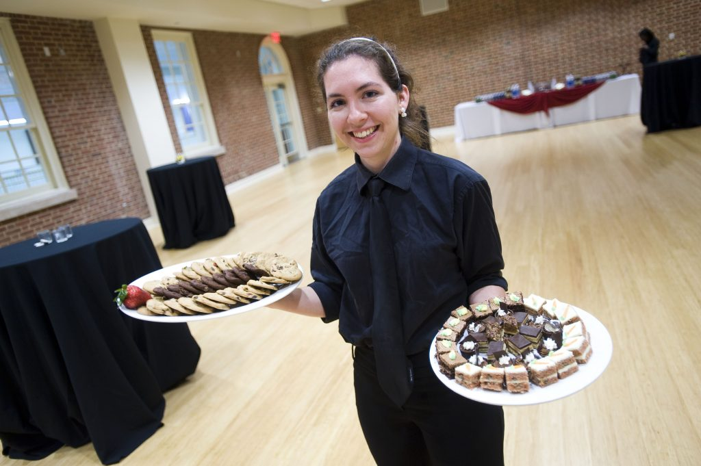 A young girl with brown hair, black shirt and black tie holding two plates of food in her hands in a ballroom