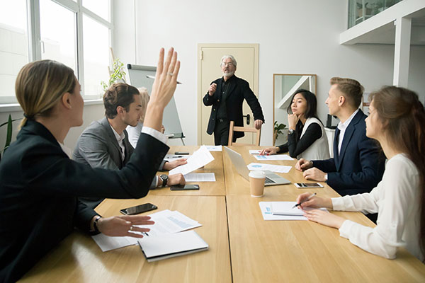 Businesswoman raising hand asking senior coach questions at team meeting