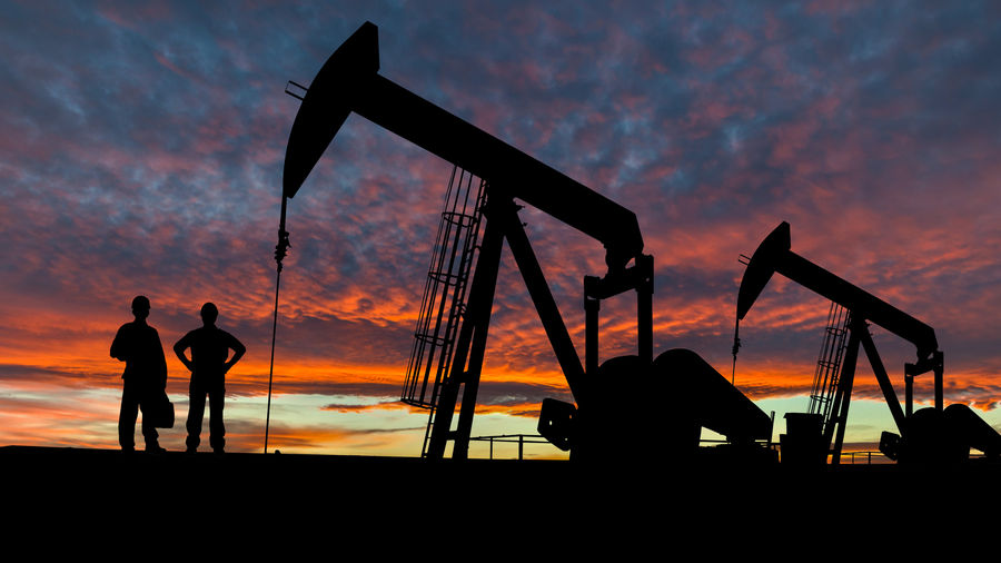 Picture of engineers looking at petroleum being pumped out by machines accross a sunset landscape