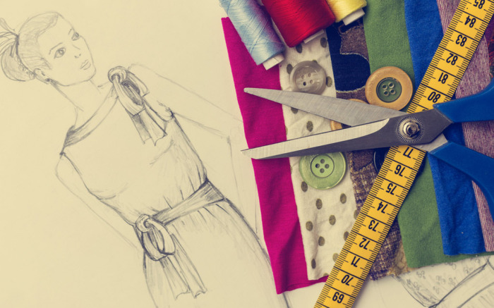 Image of tools for fashion designing including a sketch, scissors, thread, buttons and fabric