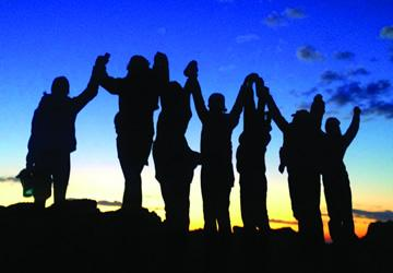 people in front of sunset holding hands in unity