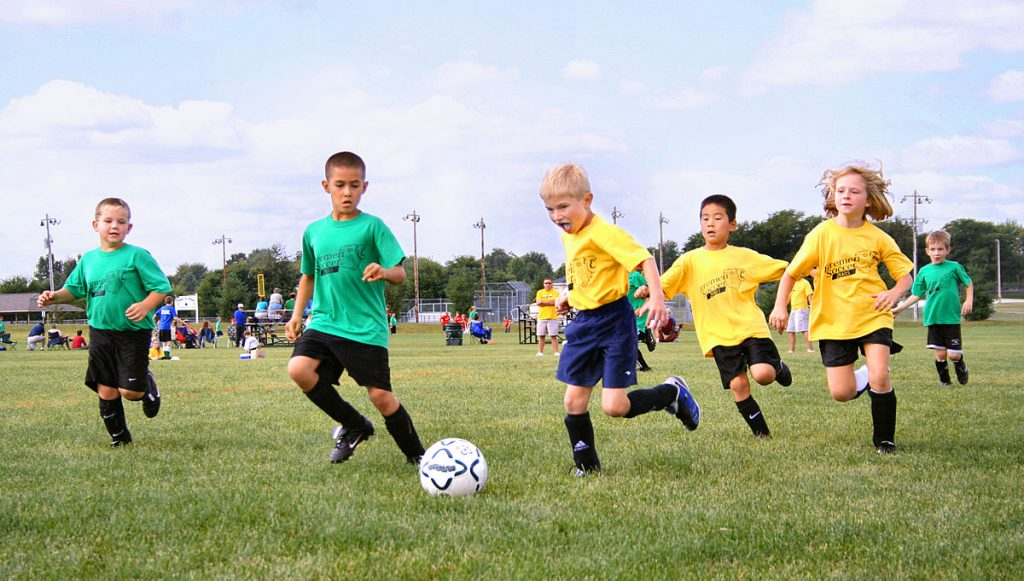 youth playing soccer on the field