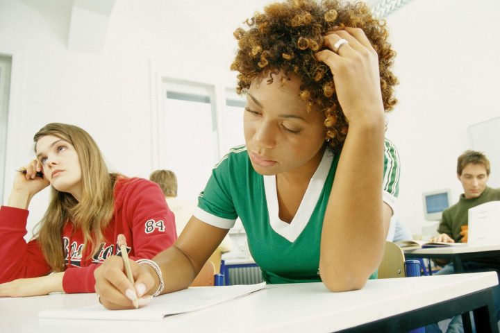 Woman studying in classroom (Image Source via AP Images)
