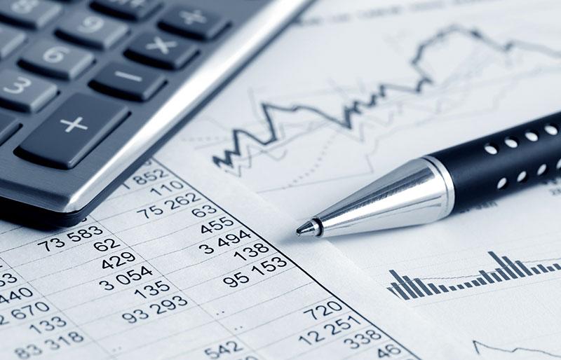 A calculator, pen, and financial records