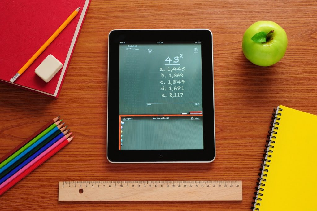 An image of an ipad with eqhations on it and notebooks and pencils around it.