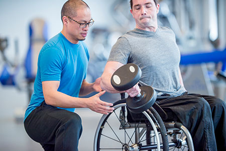 Picture of person on a wheelchair working out with physiotherapist