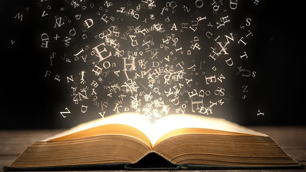 picture of an open book with letters arising from it.