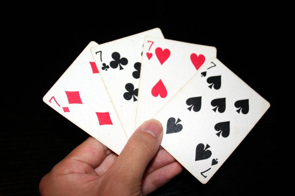 playing cards in a person's hand, all with number 7