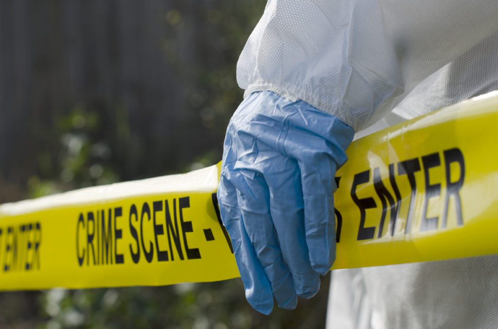 a person with gloves holding crime scene tape