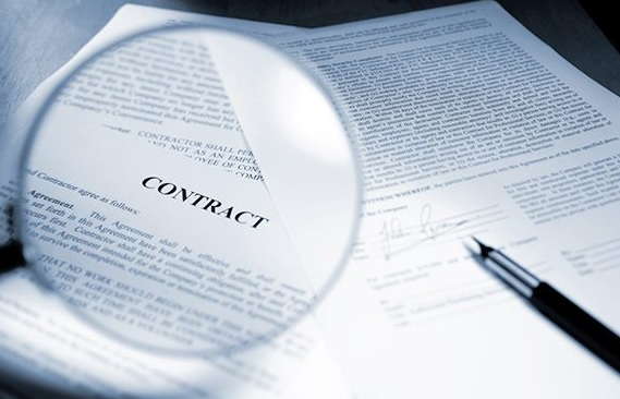 Picture of contract papers with magnifying glass