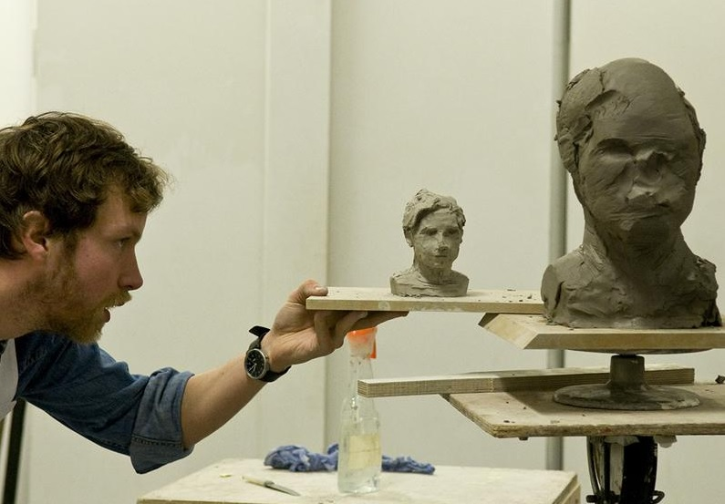 PIcture of artist looking at two clay sculptures and comparing profiles