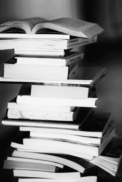 a black and white photo of a pile of books